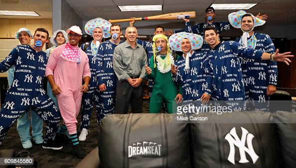 Manager Joe Girardi of the New York Yankees center poses with rookies dressed in Yankees onesies for their charter flight to Toronto following the...