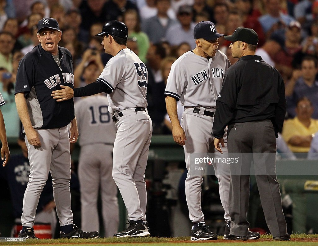 Manager <a gi-track='captionPersonalityLinkClicked' href=/galleries/search?phrase=Joe+Girardi&family=editorial&specificpeople=208659 ng-click='$event.stopPropagation()'>Joe Girardi</a> #28 of the New York Yankees defends pitching coach Larry Rothschild #58 of the Yankees after Rothschild is tossed in the seventh inning against the Boston Red Sox on August 30, 2011 at Fenway Park in Boston, Massachusetts.