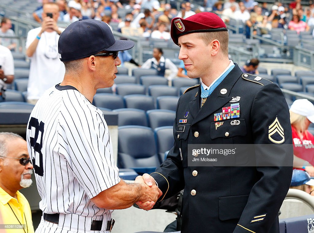 Manager Joe Girardi #28 of the New York Yankees greets Medal of Honor recipient Staff Sergeant Ryan M. Pitts before a game against the Texas Rangers at Yankee Stadium on July 24, 2014 in the Bronx borough of New York City.
