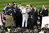 Manager Joe Girardi of the New York Yankees is interviewed as he celebrates with the trophy after their 73 win against the Philadelphia Phillies in...