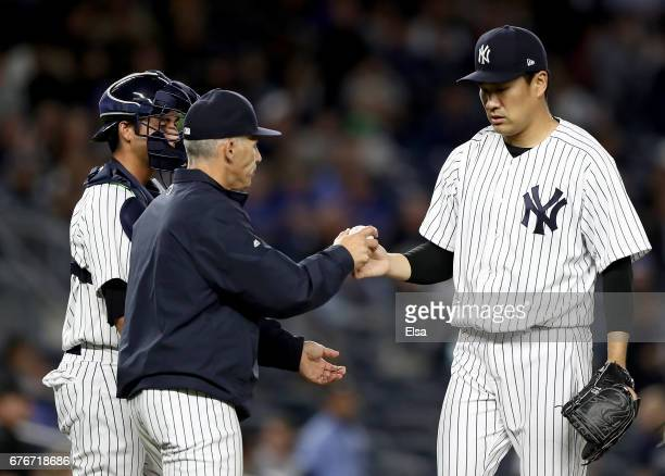 Manager Joe Girardi of the New York Yankees pulls starting pitcher Masahiro Tanaka from the game as catcher Kyle Higashioka look on in the seventh...
