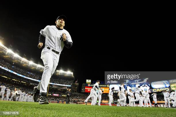 Manager Joe Girardi of the New York Yankees runs back to the dugout after pregame festivities against the Texas Rangers in Game Three of the ALCS...
