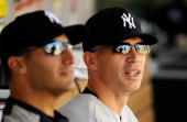 Manager Joe Girardi of the New York Yankees sits next to pitcher Andy Pettitte in the dugout before the start of the baseball game against Los...