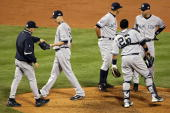 Manager Joe Girardi of the New York Yankees takes starting pitcher AJ Burnett out of the game in the bottom of the third inning against the...