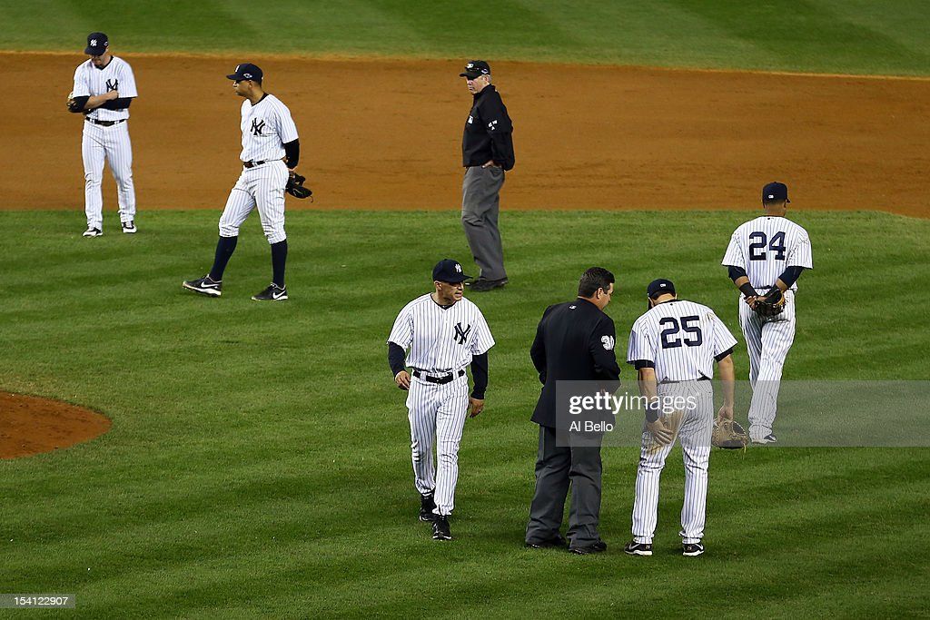Manager Joe Girardi (C) of the New York Yankees walks back to the dugout after he was thrown out of the game in the eighth inning against the Detroit Tigers during Game Two of the American League Championship Series at Yankee Stadium on October 14, 2012 in the Bronx borough of New York City.