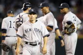 Manager Joe Girardi of the New York Yankees walks off the mound after meeting with Alex Rodriguez Francisco Cervelli Mariano Rivera Derek Jeter and...