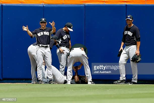 Manager Joe Girardi signals for a cart after checking on Jose Pirela of the New York Yankees after he was injured fielding a ball against the New...