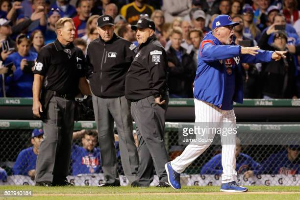 Manager Joe Maddon of the Chicago Cubs argues an overturned call with umpires and is ejected in the eighth inning during game four of the National...