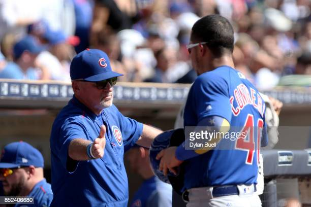Manager Joe Maddon of the Chicago Cubs congratulates Willson Contreras after scoring a run in the second inning against the Milwaukee Brewers at...