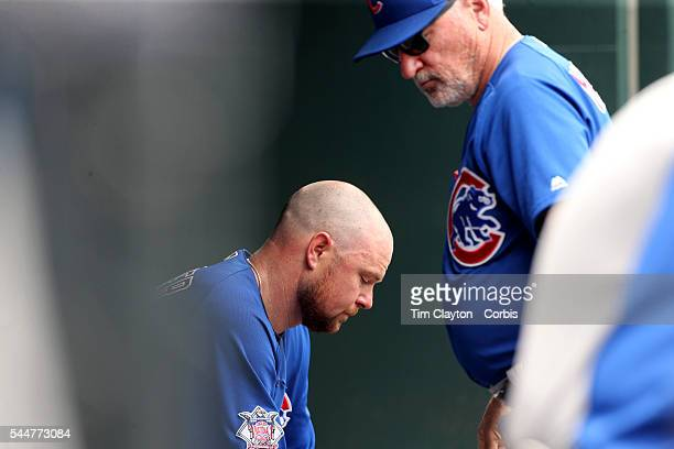 Manager Joe Maddon of the Chicago Cubs consoles pitcher Jon Lester of the Chicago Cubs after he was pulled in the second innings after giving up...