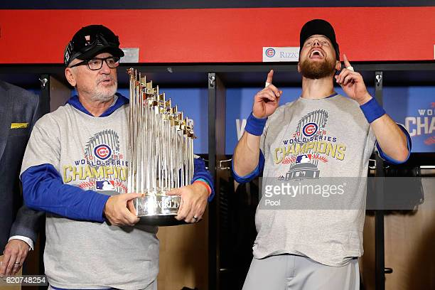 Manager Joe Maddon of the Chicago Cubs poses with The Commissioner's Trophy as Ben Zobrist reacts after the Chicago Cubs defeated the Cleveland...