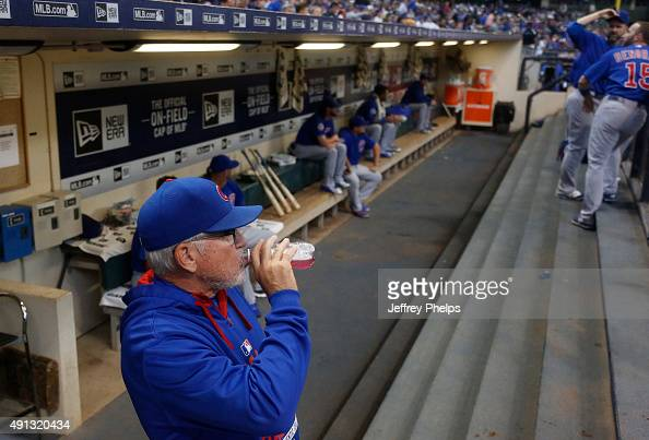 Manager Joe Maddon of the Chicago Cubs stands in the dugout before their game against the Milwaukee Brewers in a baseball game at Miller Park on...
