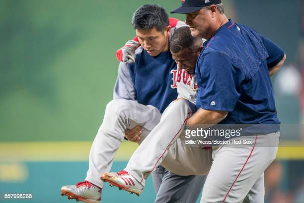Manager John Farrell and trainer Masai Takahashi tend to Eduardo Nunez of the Boston Red Sox after he was injured while running up the first base...