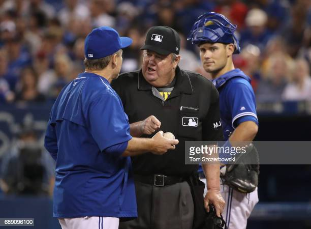 Manager John Gibbons of the Toronto Blue Jays argues a call with home plate umpire Joe West but West point to a dirt mark to bolster his case as Luke...