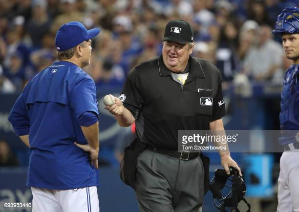 Manager John Gibbons of the Toronto Blue Jays argues a call with home plate umpire Joe West but West smiles as he points to a dirt mark to bolster...