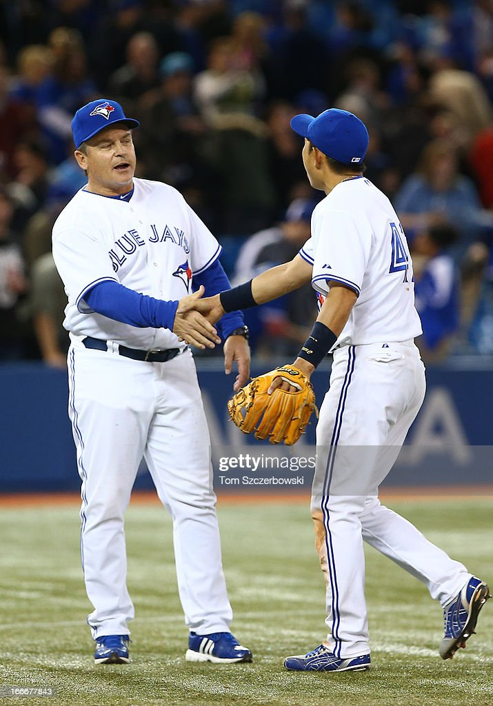 Manager <a gi-track='captionPersonalityLinkClicked' href=/galleries/search?phrase=John+Gibbons&family=editorial&specificpeople=218120 ng-click='$event.stopPropagation()'>John Gibbons</a> of the Toronto Blue Jays congratulates <a gi-track='captionPersonalityLinkClicked' href=/galleries/search?phrase=Munenori+Kawasaki&family=editorial&specificpeople=690355 ng-click='$event.stopPropagation()'>Munenori Kawasaki</a> after their win during MLB game action against the Chicago White Sox on April 15, 2013 at Rogers Centre in Toronto, Ontario, Canada. All uniformed team members are wearing jersey number 42 in honor of Jackie Robinson Day.
