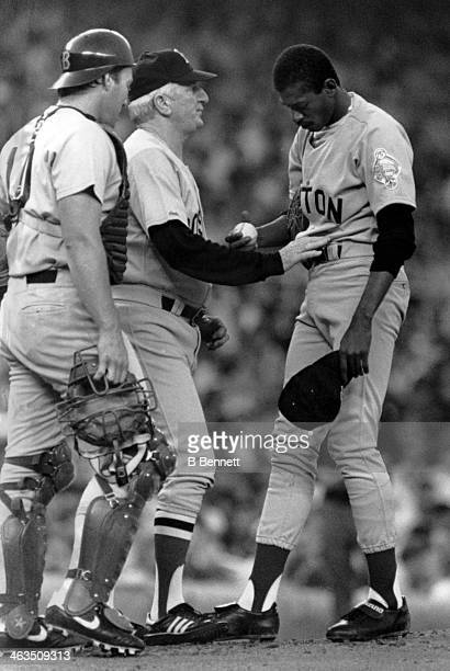 Manager John McNamara of the Boston Red Sox talks with pitcher Dennis 'Oil Can' Boyd as catcher Rich Gedman looks on during the game against the New...