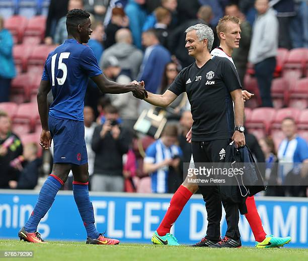 Manager Jose Mourinho of Manchester United congratulates Axel Tuanzebe after the preseason friendly match between Wigan Athletic and Manchester...