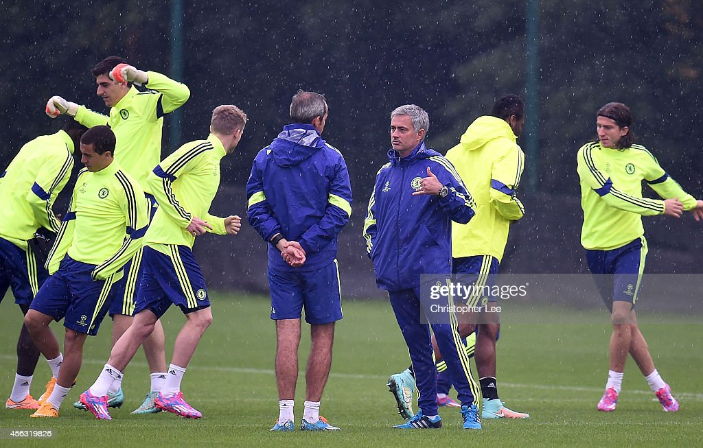 Manager Jose Mourinho talks to his assistant as his players warm up behind him during the Chelsea Training Session at Chelsea Training Ground on September 29, 2014 in Cobham, England.