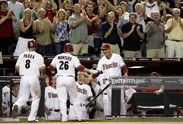 Manager Kirk Gibson and Collin Cowgill of the Arizona Diamondbacks highfive Miguel Montero after he hit a threerun home run against the Colorado...