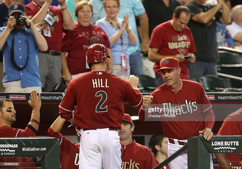 Manager <a gi-track='captionPersonalityLinkClicked' href=/galleries/search?phrase=Kirk+Gibson&family=editorial&specificpeople=207042 ng-click='$event.stopPropagation()'>Kirk Gibson</a> #23 of the Arizona Diamondbacks high-fivess <a gi-track='captionPersonalityLinkClicked' href=/galleries/search?phrase=Aaron+Hill+-+Baseball+Player&family=editorial&specificpeople=239242 ng-click='$event.stopPropagation()'>Aaron Hill</a> #2 after Hill hit a solo home run against the Washington Nationals during the fourth inning of the MLB game at Chase Field on May 14, 2014 in Phoenix, Arizona. The Nationals defeated the Diamondbacks 5-1.