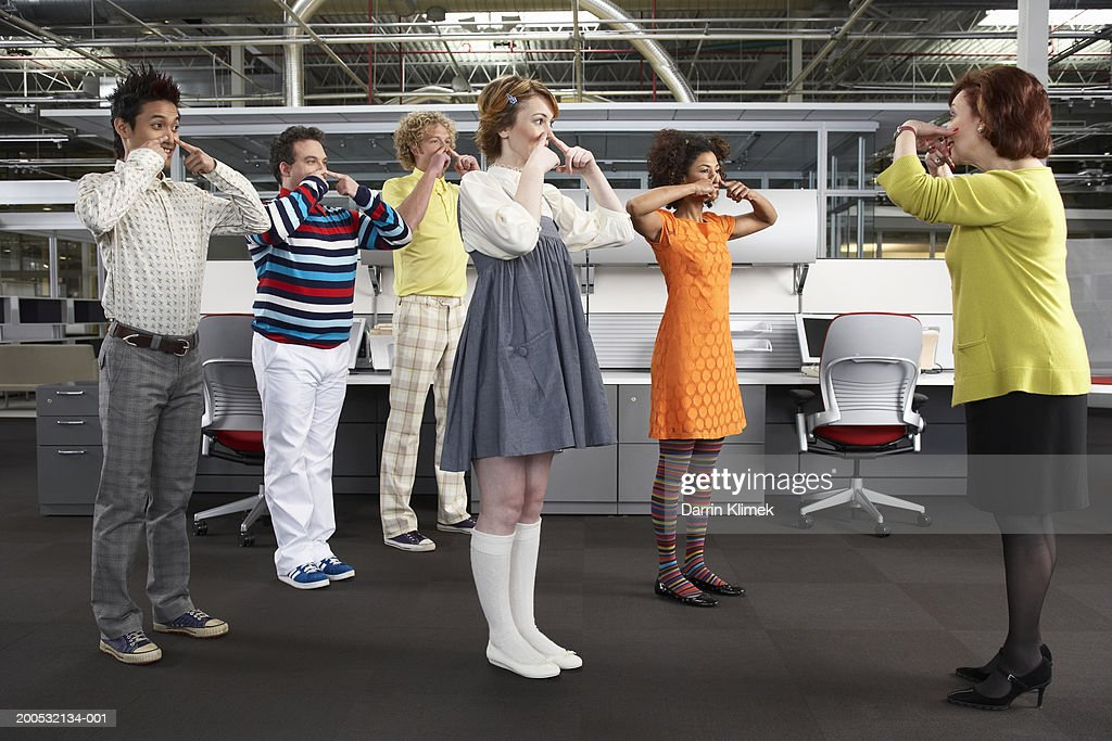 Manager leading workers in game, workers in childlike clothing : Stock Photo