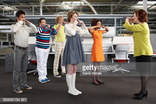 Manager leading workers in game, workers in childlike clothing : Bildbanksbilder