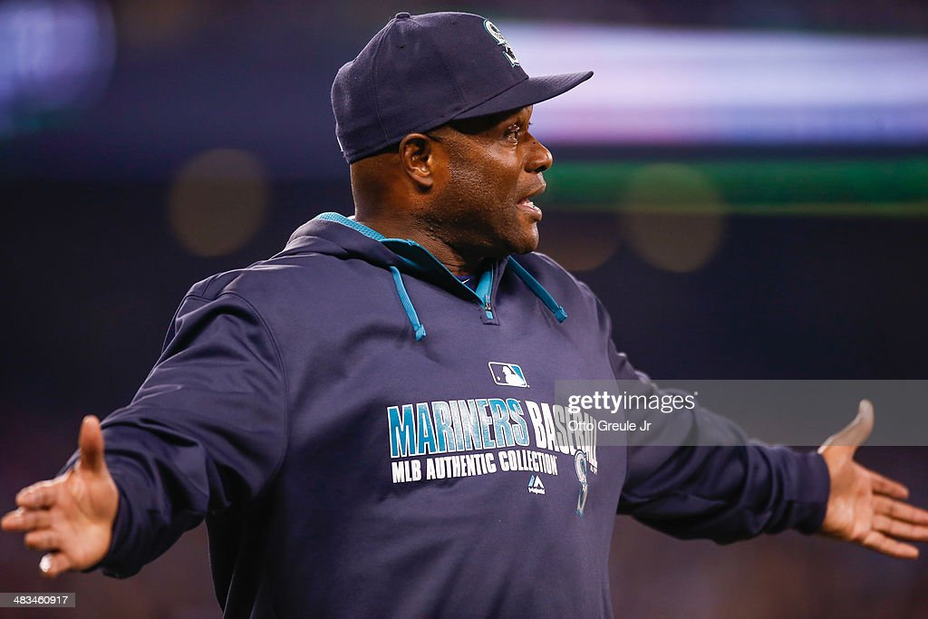 Manager Lloyd McClendon #23 of the Seattle Mariners questions why Corey Hart was only awarded a single after successfully challenging a dropped ball by center fielder Mike Trout of the Los Angeles Angels of Anaheim in the fifth inning on Opening Day at Safeco Field on April 8, 2014 in Seattle, Washington.