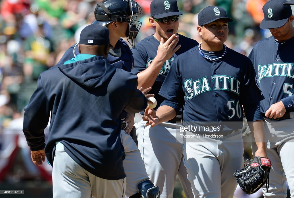 Manager Lloyd McClendon #23 of the Seattle Mariners takes the ball from pitcher Erasmo Ramirez #50 taking him out of the game against the Oakland Athletics in the bottom of the fifth inning at O.co Coliseum on April 6, 2014 in Oakland, California.
