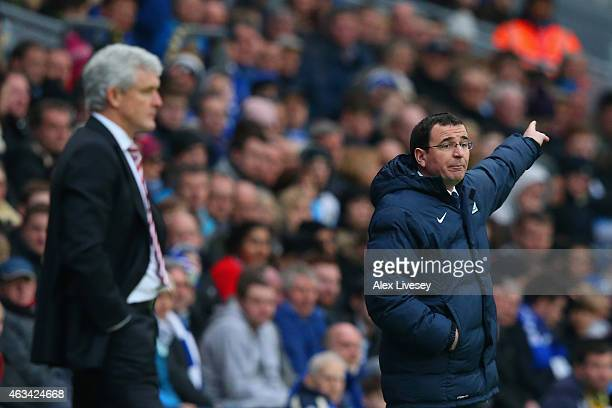 Manager Mark Hughes of Stoke City looks on as Manager Gary Bowyer of Blackburn gives instructions during the FA Cup Fifth Round match between...