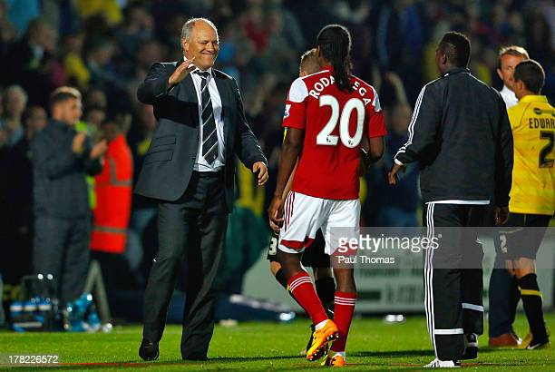 Manager Martin Jol of Fulham congratulates his player Hugo Rodallega after the Capital One Cup Second Round match between Burton Albion and Fulham at...