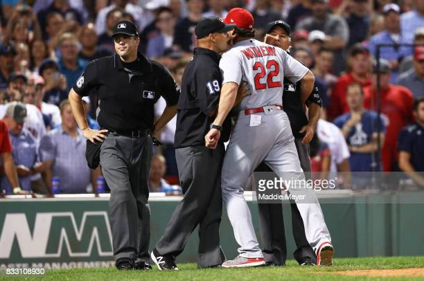 Manager Mike Matheny of the St Louis Cardinals is held back by Umpire Vic Carapazza before being ejected during the ninth inning at Fenway Park on...