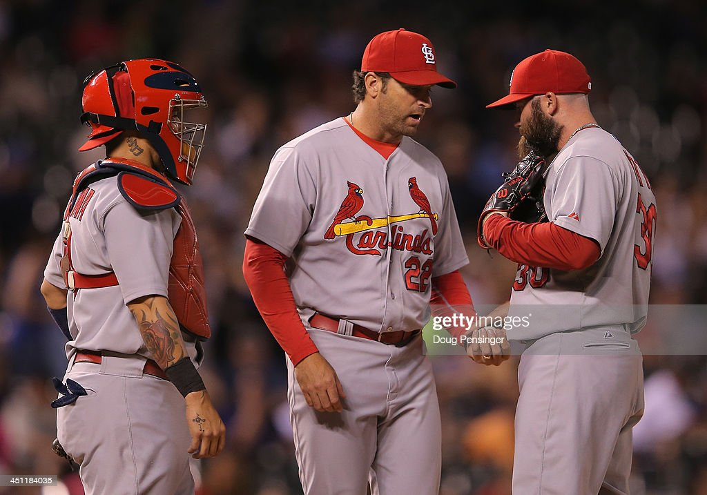 Manager Mike Matheny #22 of the St. Louis Cardinals removes pitcher Jason Motte #30 of the St. Louis Cardinals from the game against the Colorado Rockies in the eighth inning as catcher Yadier Molina #4 of the St. Louis Cardinals looks on at Coors Field on June 24, 2014 in Denver, Colorado.