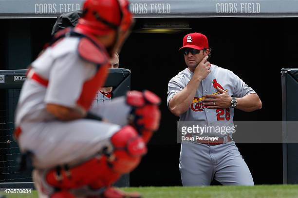 Manager Mike Matheny of the St Louis Cardinals sends signals from the dugout to catcher Yadier Molina of the St Louis Cardinals as they face the...