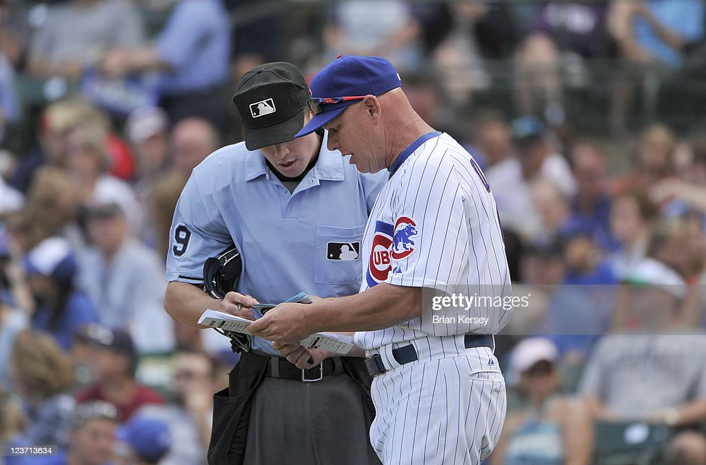 Manager Mike Quade #8 (R) of the Chicago Cubs makes a double switch with home plate umpire Cory Blaser during the seventh inning against the Pittsburgh Pirates at Wrigley Field on September 4, 2011 in Chicago, Illinois. The Cubs won 6-3.