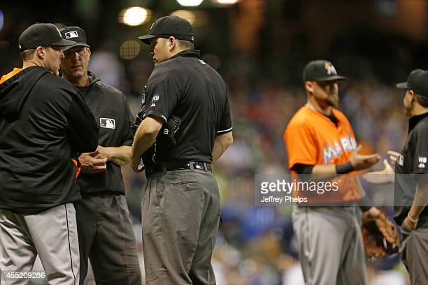 Manager Mike Redmond of the Miami Marlins and Casey McGehee question a call against the Milwaukee Brewers in the third inning at Miller Park on...