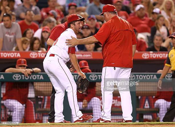 Manager Mike Scioscia and trainer Adam Nevala of the Los Angeles Angels of Anaheim tend to pitcher Huston Street as he comes out of the game with an...