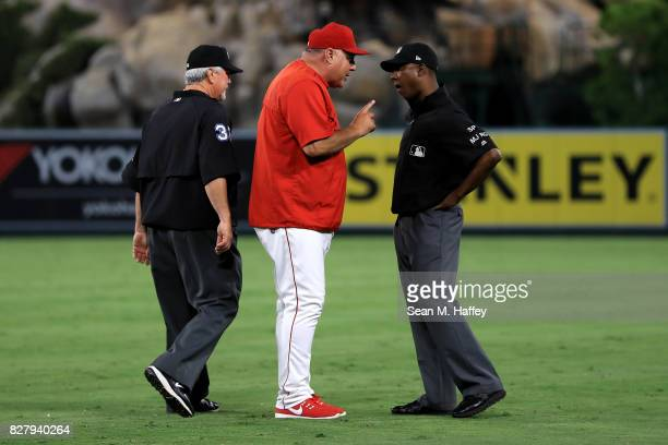 Manager Mike Scioscia argues a called third strike on Albert Pujols of the Los Angeles Angels of Anaheim with first base umpire Ramon De Jesus and...