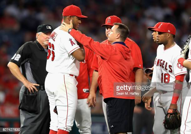 Manager Mike Scioscia Luis Valbuena and trainer talk with JC Ramirez of the Los Angeles Angels of Anaheim after he was hit by a broken bat during the...