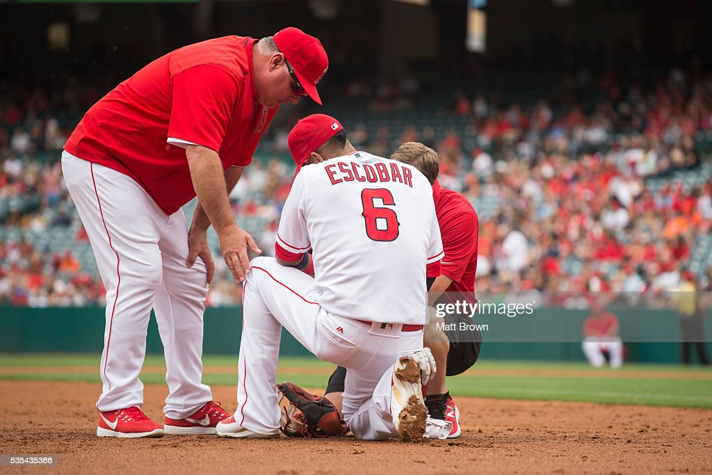 Manager <a gi-track='captionPersonalityLinkClicked' href=/galleries/search?phrase=Mike+Scioscia&family=editorial&specificpeople=206319 ng-click='$event.stopPropagation()'>Mike Scioscia</a> #14 of the Los Angeles Angels of Anaheim and athletic trainer Adam Nevala examine <a gi-track='captionPersonalityLinkClicked' href=/galleries/search?phrase=Yunel+Escobar&family=editorial&specificpeople=757358 ng-click='$event.stopPropagation()'>Yunel Escobar</a> #6 before Escobar left the game with a wrist injury as a result of being struck by a line drive during the third inning of the game against the Houston Astros at Angel Stadium of Anaheim on May 29, 2016 in Anaheim, California.