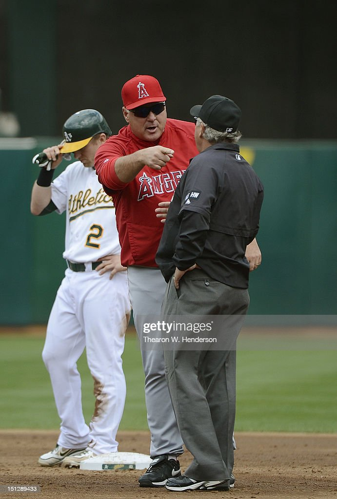 Manager <a gi-track='captionPersonalityLinkClicked' href=/galleries/search?phrase=Mike+Scioscia&family=editorial&specificpeople=206319 ng-click='$event.stopPropagation()'>Mike Scioscia</a> #14 of the Los Angeles Angels of Anaheim argues a safe call at second base with umpire Tom Hallion #20 in the third inning against the Oakland Athletics at O.co Coliseum on September 5, 2012 in Oakland, California.