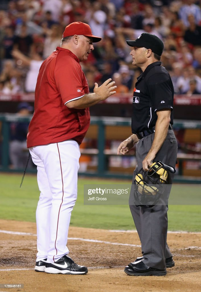 Manager <a gi-track='captionPersonalityLinkClicked' href=/galleries/search?phrase=Mike+Scioscia&family=editorial&specificpeople=206319 ng-click='$event.stopPropagation()'>Mike Scioscia</a> #14 of the Los Angeles Angels of Anaheim argues with home plate umpire Dan Iassonga in the fourth inning against the Cleveland Indians at Angel Stadium of Anaheim on August 19, 2013 in Anaheim, California. The Indians defeated the Angels 5-2.