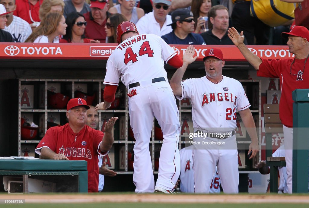 Manager <a gi-track='captionPersonalityLinkClicked' href=/galleries/search?phrase=Mike+Scioscia&family=editorial&specificpeople=206319 ng-click='$event.stopPropagation()'>Mike Scioscia</a> of the Los Angeles Angels of Anaheim celebrates with his player <a gi-track='captionPersonalityLinkClicked' href=/galleries/search?phrase=Mark+Trumbo&family=editorial&specificpeople=4921667 ng-click='$event.stopPropagation()'>Mark Trumbo</a> #44 after Trumbo scored on a single by Erick Aybar #2 (not in photo) in the sixth inning during the MLB game against the New York Yankees at Angel Stadium of Anaheim on June 15, 2013 in Anaheim, California. The Angels defeated the Yankees 6-2.
