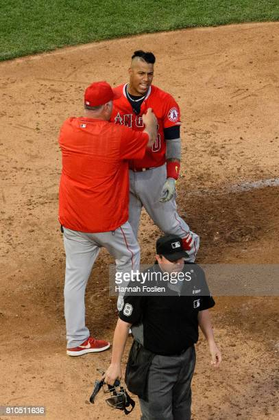 Manager Mike Scioscia of the Los Angeles Angels of Anaheim gets between Yunel Escobar and home plate umpire Doug Eddings after Escobar was ejected...