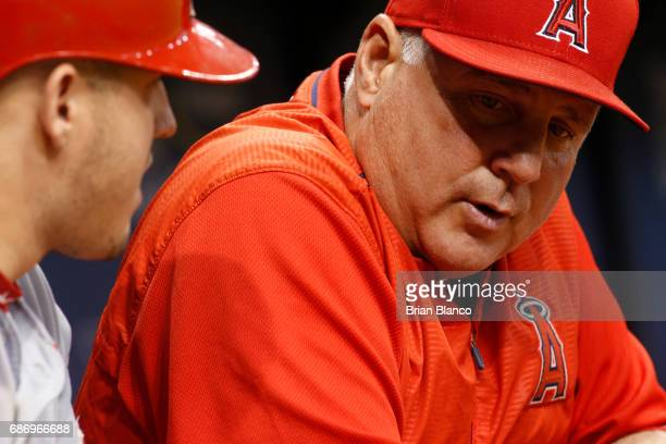 Manager Mike Scioscia of the Los Angeles Angels speaks with Mike Trout in the dugout during the fifth inning of a game against the Tampa Bay Rays on...
