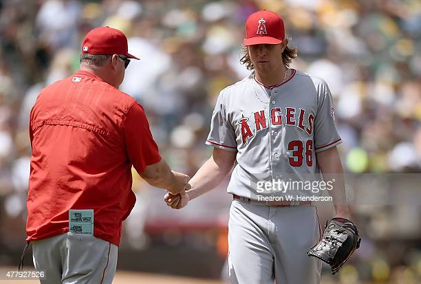 Manager Mike Scioscia of the Los Angeles Angels of Anaheim takes the ball from pitcher Jered Weaver taking him out of the game against the Oakland...