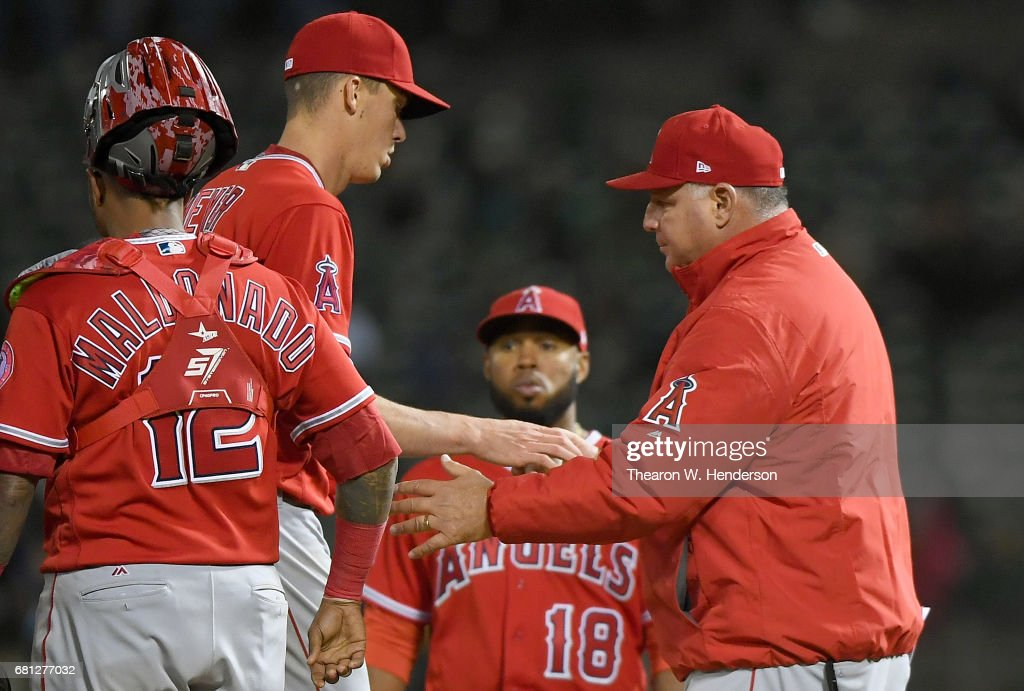 Manager Mike Scioscia #14 of the Los Angeles Angels of Anaheim takes the ball from starting pitcher Alex Meyer #23 taking him out of the game against the Oakland Athletics in the bottom of the six inning at Oakland Alameda Coliseum on May 9, 2017 in Oakland, California.