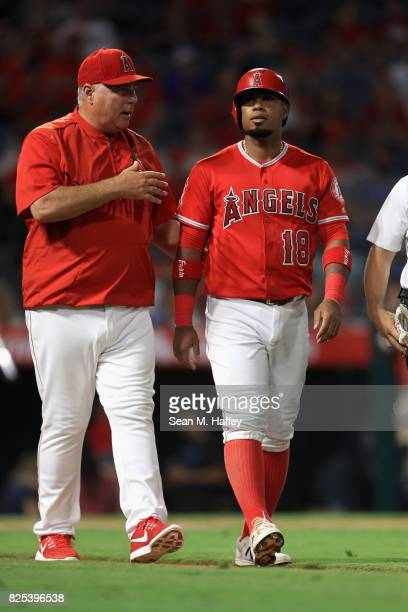 Manager Mike Scioscia walks Luis Valbuena of the Los Angeles Angels of Anaheim to first base after he was hit by a pitch during the seventh inning of...