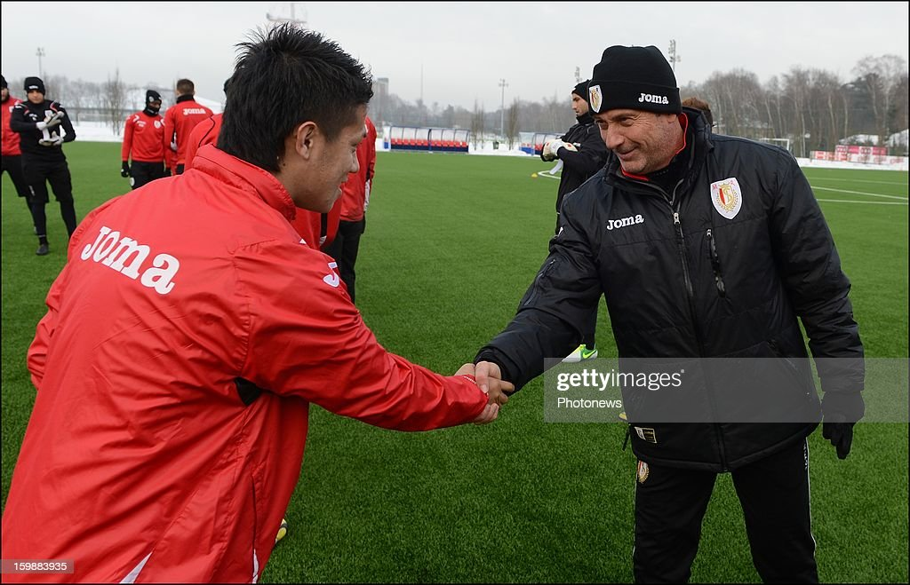 Manager Mircea Rednic shakes hands with new signing Yuji Ono of Standard Liege attend a training session on January 22, 2013 in Liege, Belgium.