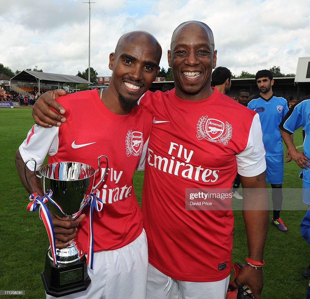 Manager Mo Farah and Ian Wright of Arsenal Legends XI pose with the trophy after the charity football match between Arsenal Legends XI and World...
